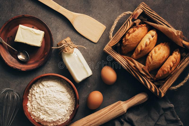Baking background, ingredients for cooking pies, flour, butter, milk, eggs. Traditional Russians baked patties, pirozhki. Overhead royalty free stock image