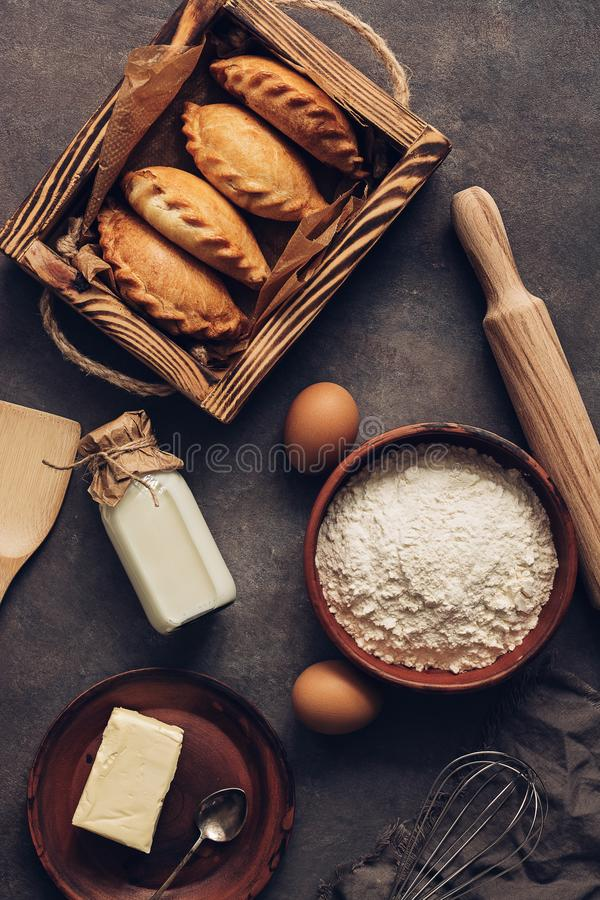 Baking background, ingredients for cooking pies, flour, butter, milk, eggs. Traditional Russians baked patties, pirozhki. View royalty free stock photography