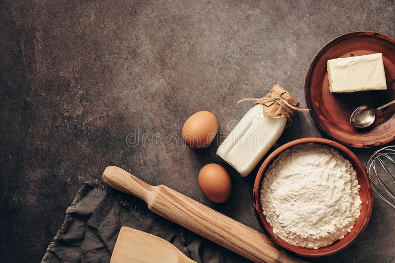 Baking background with ingredients, flour, rolling pin, bottle of milk, butter and eggs on a dark rustic background. Top view, stock photos