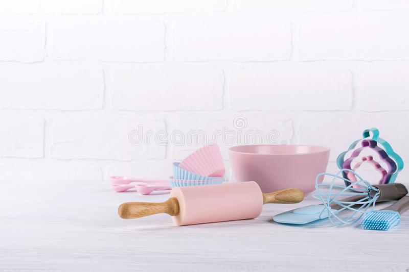 Baking background with kitchen tools: rolling pin, wooden spoons, whisk, sieve, bakeware and shape cookie cutter on white. Wooden background stock images