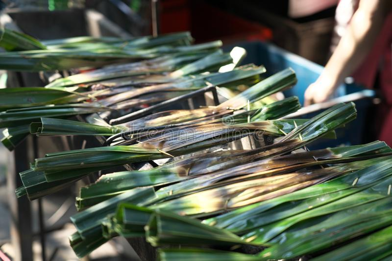 Baking banana leaves for wrapping sticky rice at open market in Chachoengsao, Thailand stock photo
