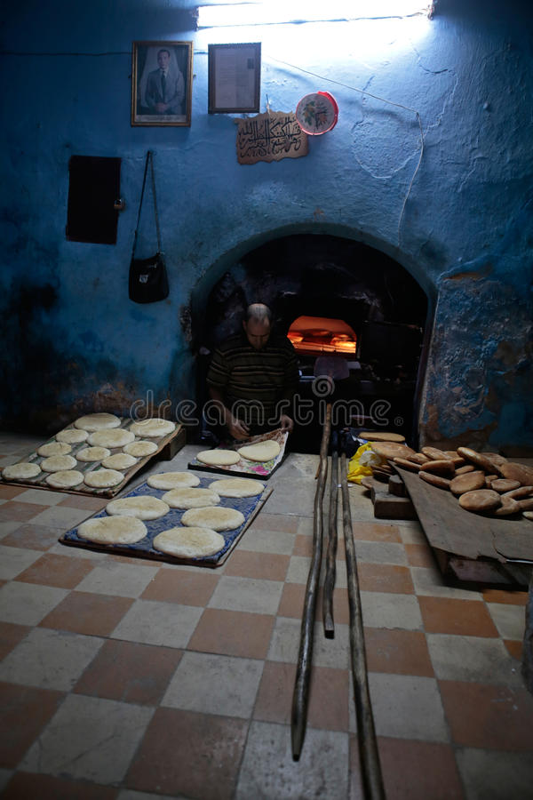 Baking bread pieces in ancient Medina of Fez in Morocco. A baker prepares the bread before placing it into an antique wood oven in a local bakery in the city of stock image