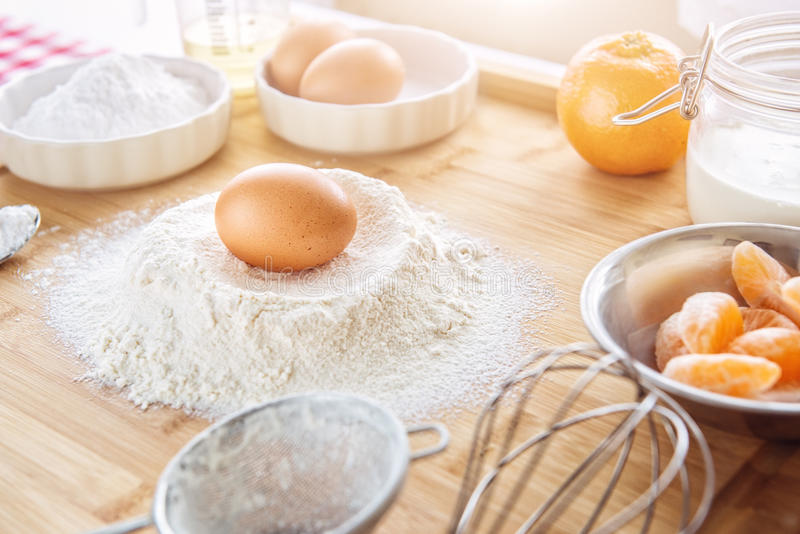 Baking cake in kitchen - dough recipe ingredients with fruit on wood table. Baking cake in kitchen - dough recipe ingredients (eggs, flour, milk, sugar) with stock images