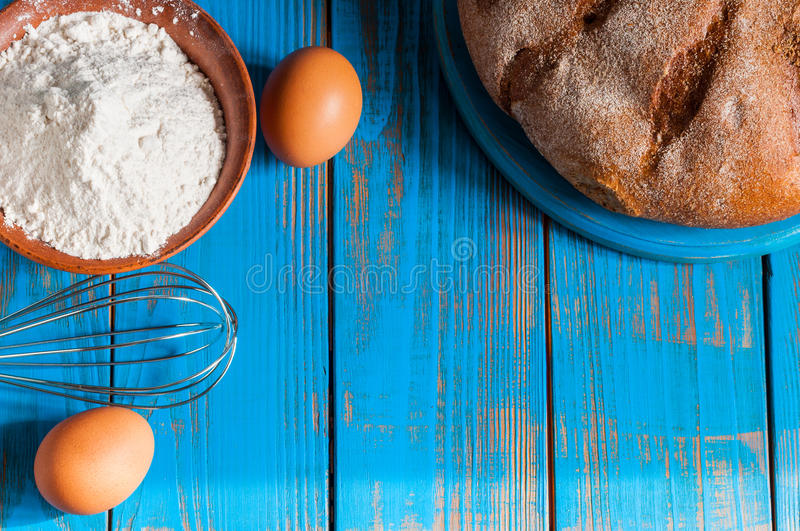 Baking cake in rural kitchen - dough recipe. Ingredients eggs, flour, butter, bread and whisk on vintage wood table from above. Rustic background with free text stock image