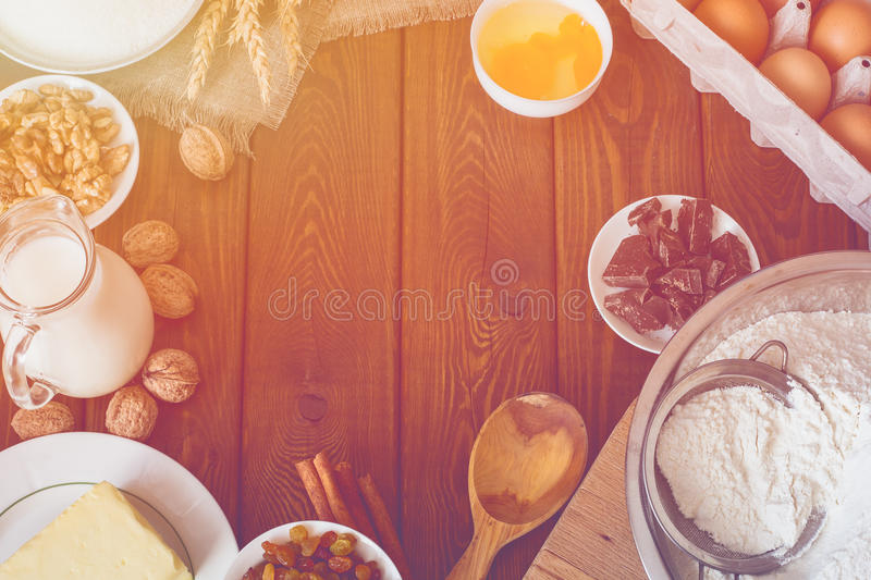 Baking cake in rural kitchen, dough recipe ingredients : eggs, flour, milk. Butter, oil, walnuts and raisins on vintage wood table from above. Rustic stock images