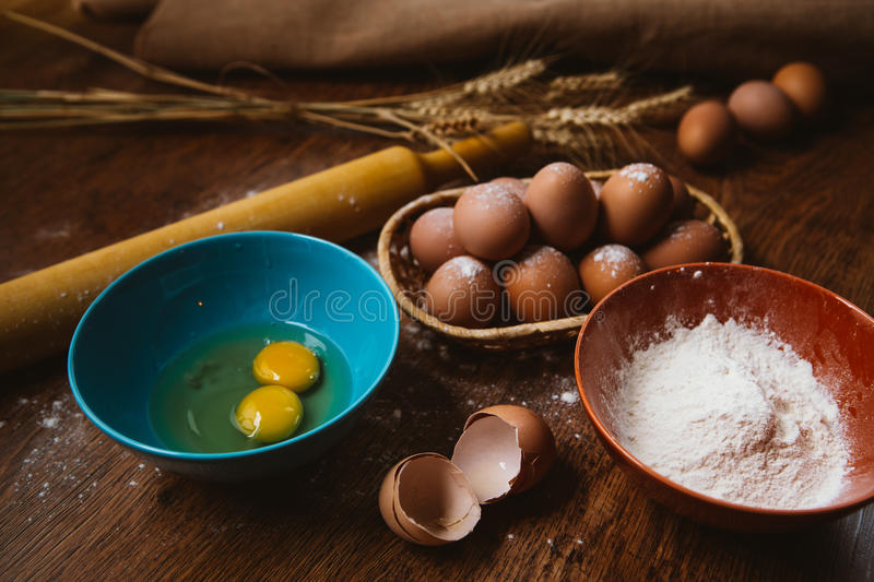 Baking cake in rural kitchen - dough recipe ingredients eggs, flour, sugar on vintage wooden table from above. Baking cake in rural kitchen - dough recipe royalty free stock images