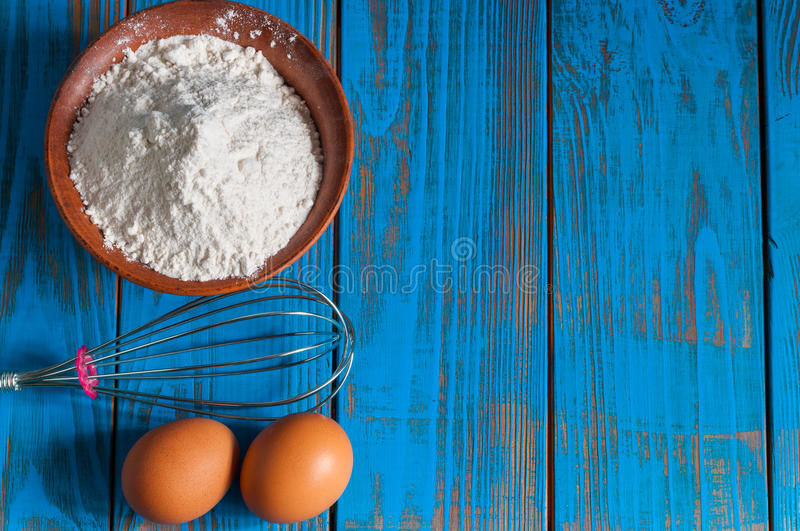 Baking cake in rural kitchen - dough recipe. Ingredients eggs, flour and whisk on vintage wood table from above. Rustic background with free text space stock photography