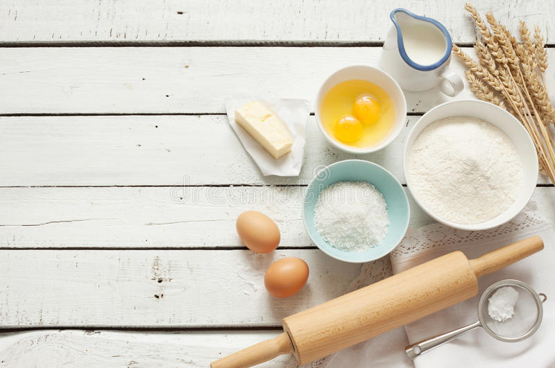 Baking cake in rustic kitchen - dough recipe ingredients on white wooden table. Baking cake in rustic kitchen - dough recipe ingredients (eggs, flour, milk stock images