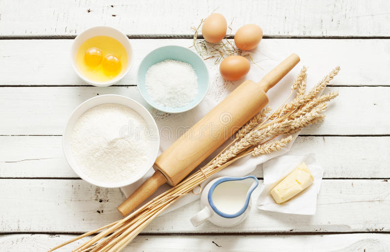 Baking cake in rustic kitchen - dough recipe ingredients on white wooden table. Baking cake in rustic kitchen - dough recipe ingredients (eggs, flour, milk royalty free stock photography