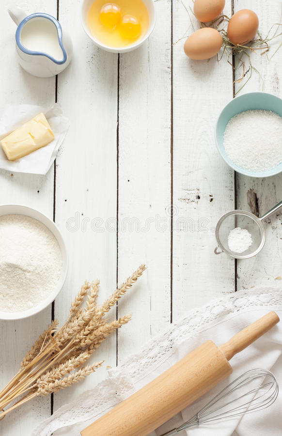 Baking cake in rustic kitchen - dough recipe ingredients on white wooden table. Baking cake in rustic kitchen - dough recipe ingredients (eggs, flour, milk stock photography