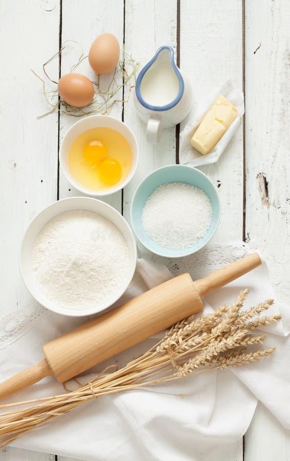 Baking cake in rustic kitchen - dough recipe ingredients on white wooden table. Baking cake in rustic kitchen - dough recipe ingredients (eggs, flour, milk royalty free stock image