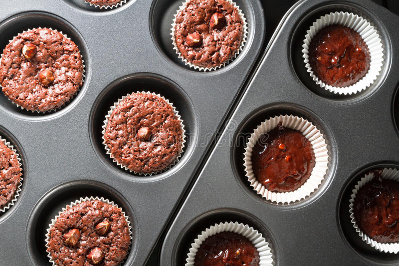 Before and after baking chocolate muffins royalty free stock photos