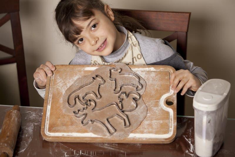 Baking christmas cookies. Little girl baking christmas cookies stock image