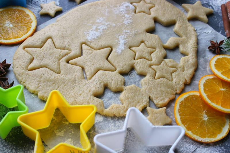 Baking Christmas gingerbread, flour sprinkled dough on a wooden table, molds in the form of stars stock image