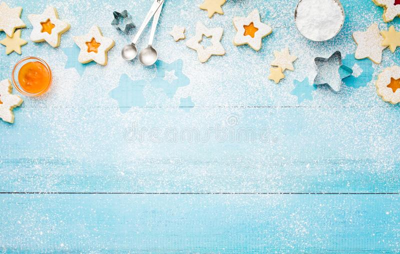 Baking Christmas Linzer Cookies Border. Christmas Linzer cookies border with icing sugar and apricot jam on a blue wooden background royalty free stock photos