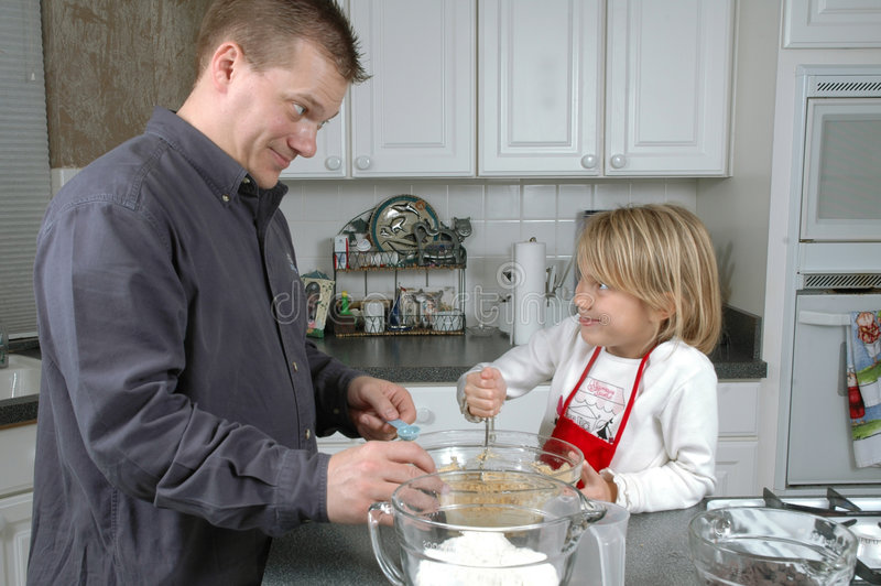 Baking Cookies Together. Father and Daughter bake some cookies together in the kitchen