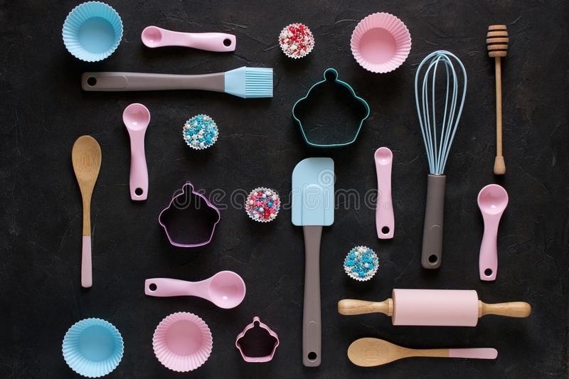 Baking and cooking concept. Pattern made of cookie cutters, whisk, roller pin and kitchen bake tools for making sweets. Dark background. Top view of a holiday royalty free stock images