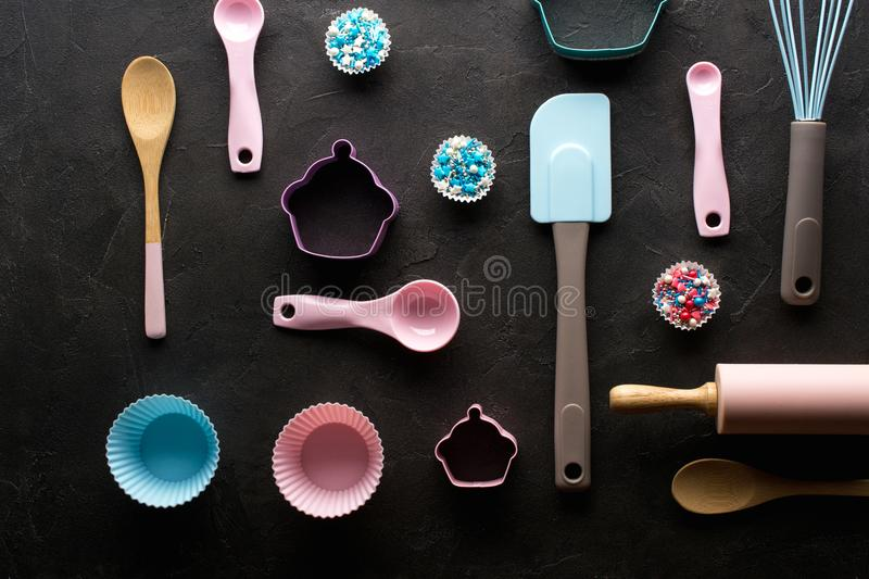 Baking and cooking concept. Pattern made of cookie cutters, whisk, roller pin and kitchen bake tools for making sweets. Dark background. Top view of a holiday stock images