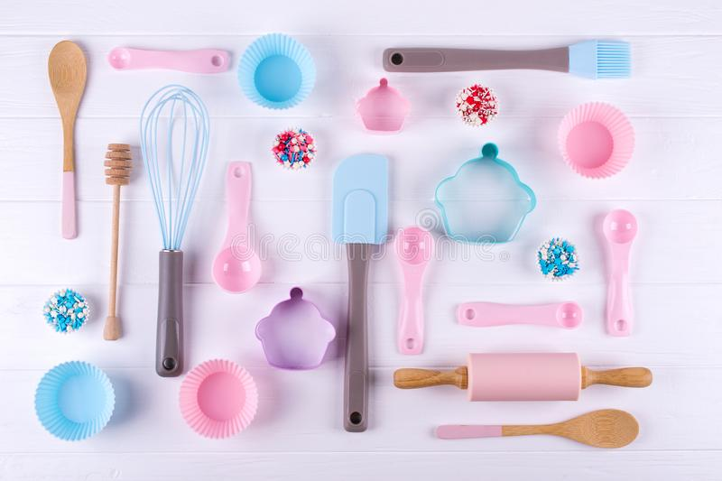 Baking and cooking concept. Pattern made of cookie cutters, whisk, roller pin and kitchen bake tools for making sweets. White background. Top view of a holiday stock image