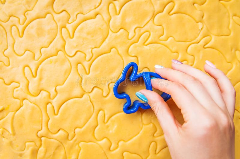 Baking Easter biscuits. Process of cutting rabbit-shaped cookies Woman holds a mold. royalty free stock photo