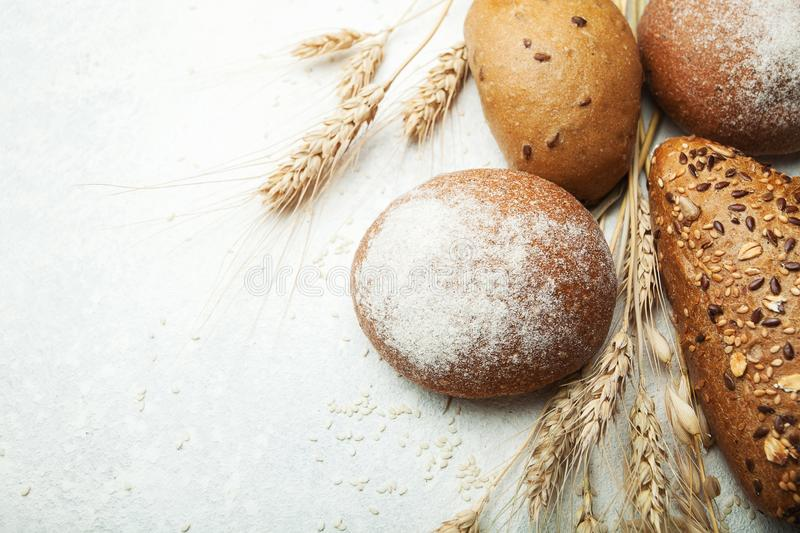Baking fresh wheat bread with flour and grain on a white table, top view stock photography