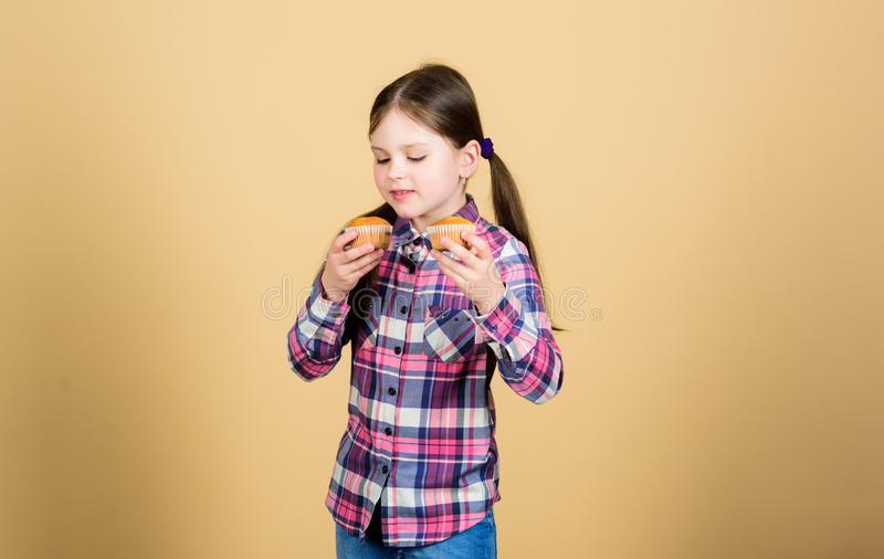 Baking freshness every day. Cute small child enjoy baking and eating sweet food. Adorable little girl holding freshly. Baked cupcakes. Following the best baking stock photos