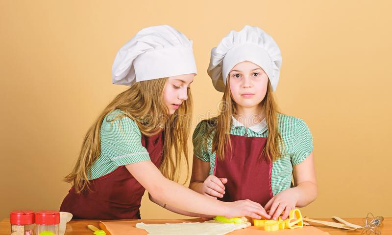 Baking ginger cookies. Girls sisters having fun ginger dough. Kids baking cookies together. Kids aprons and chef hats. Cooking. Homemade cookies best. Family royalty free stock image