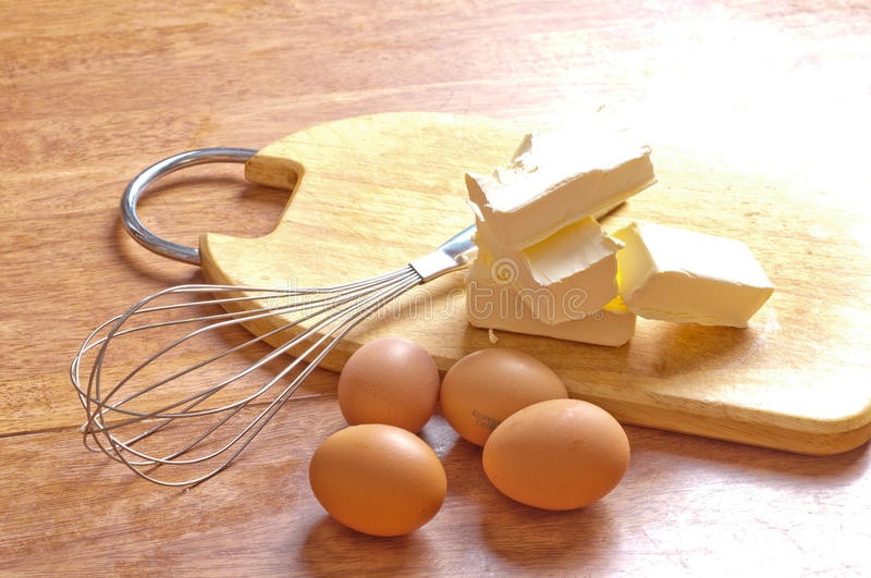Baking ingredients. With eggbeater and cake tin on a wooden kitchen-board stock image