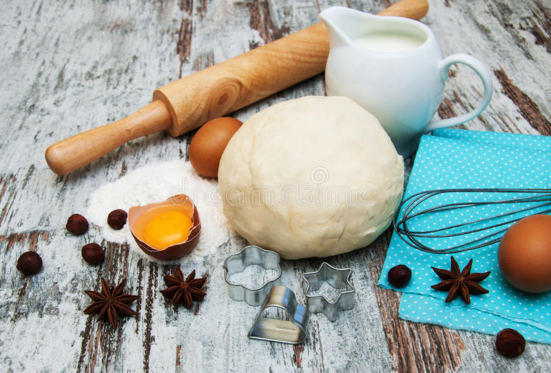 Baking ingredients. Eggs, dough, and spices on a wooden background stock images