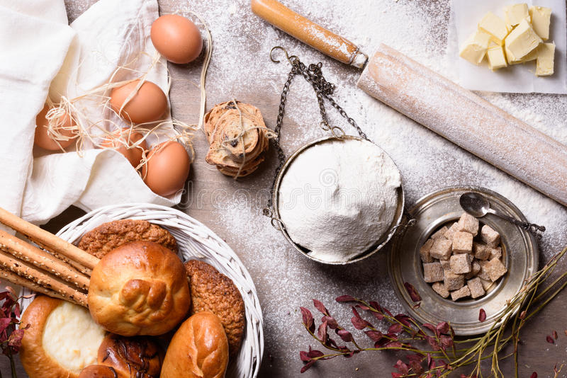 Baking ingredients - flour, butter, eggs, sugar. Baked flour-based food: bread, cookies, cakes, pastries, pies. Top view. Baking ingredients - flour, butter royalty free stock photo