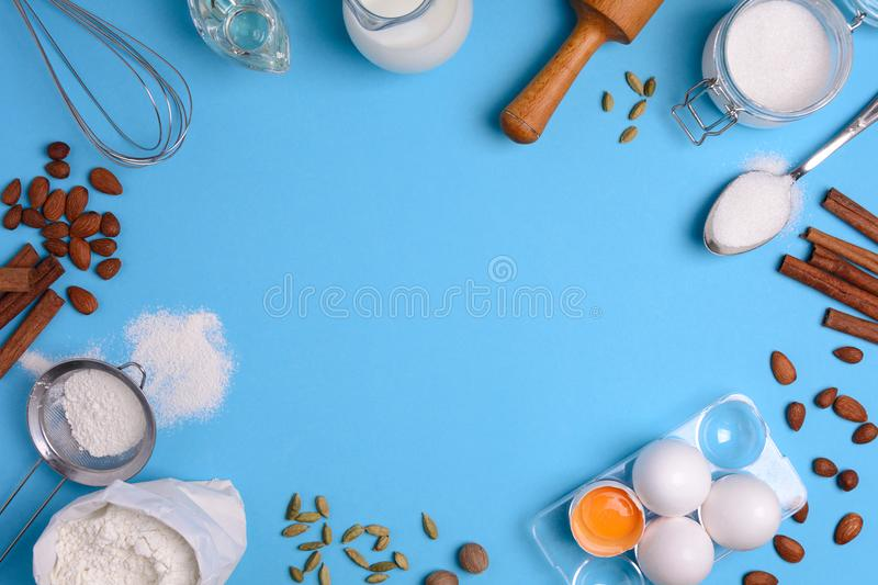 Baking ingredients for homemade pastry on blue background. Bake sweet cake dessert concept. Top view. Flat lay stock photo
