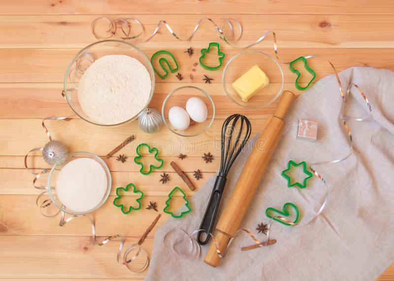 Baking ingredients, spices, whisk, rolling pin and cookie cutters. Flour, eggs, sugar, butter, spices, whisk, rolling pin and cookie cutters for baking christmas stock photos