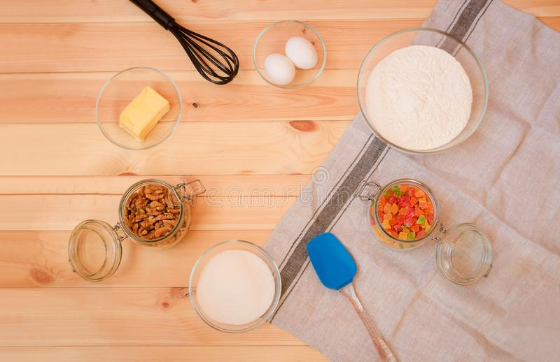 Baking ingredients, whisk and spatula on wooden background. Top view, copy space stock image