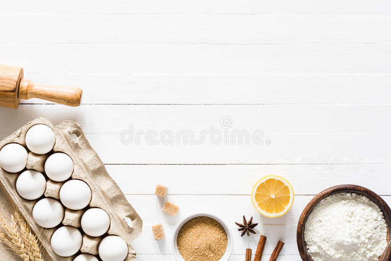Baking ingredients on white wooden table background. Baking ingredients on white table. Box of white eggs, brown sugar, spices, lemon, white flour and rolling royalty free stock photos