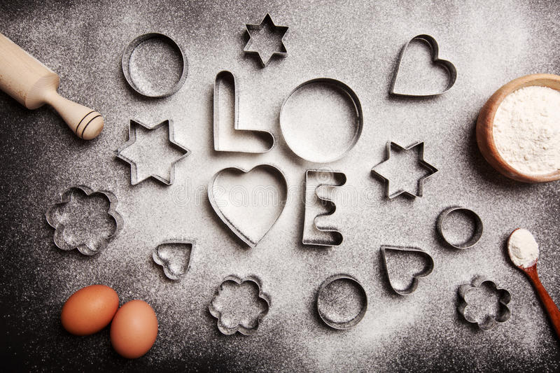 Baking with love. Heart - shaped cookie cutters, flour and word Love , made with it, and other stuff for baking cookies, lying on black table stock photos