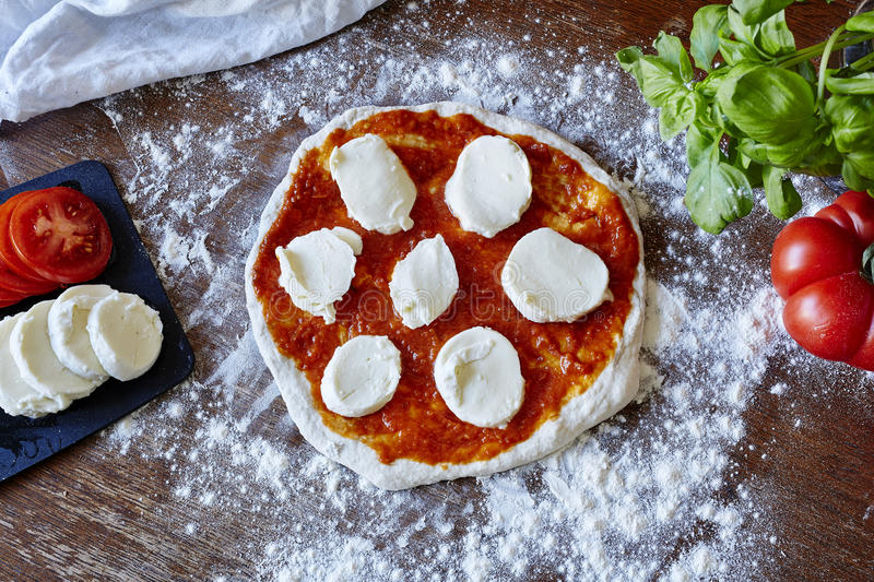 Baking pizza rolled out dough sauce fresh tomatoes and mozzarella stock photo