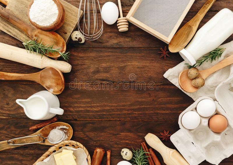 Baking or recipe ingredients eggs, flour, milk, butter, sugar on wooden table from above royalty free stock photo