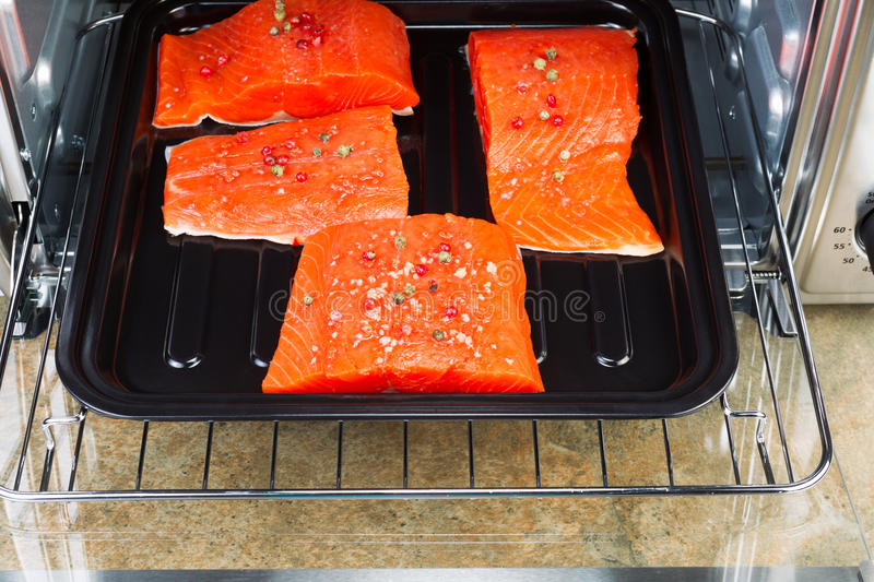 Baking Salmon in Oven. Horizontal photo of Wild Red Salmon pieces coated with dried red peppercorns and sea salt inside oven with stone counter top underneath royalty free stock image