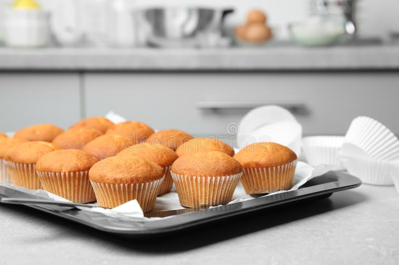 Baking sheet with delicious cupcakes. On kitchen table stock image