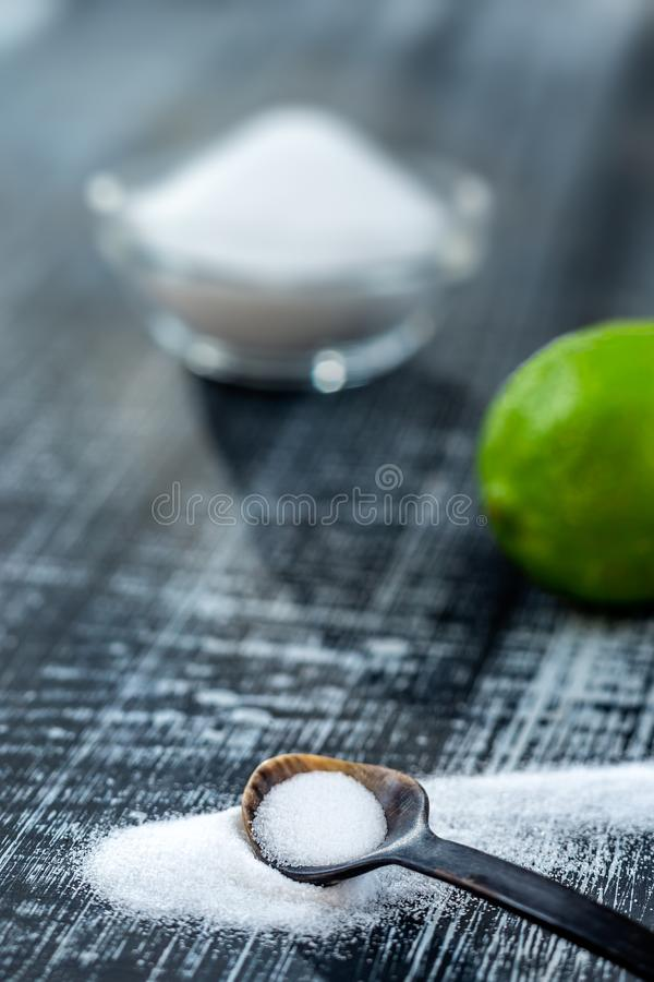 Baking soda - sodium bicarbonate and lemon. Natural, powder on a grey wooden background. Baking soda - sodium bicarbonate and lemon. Natural, powder grey wooen stock image