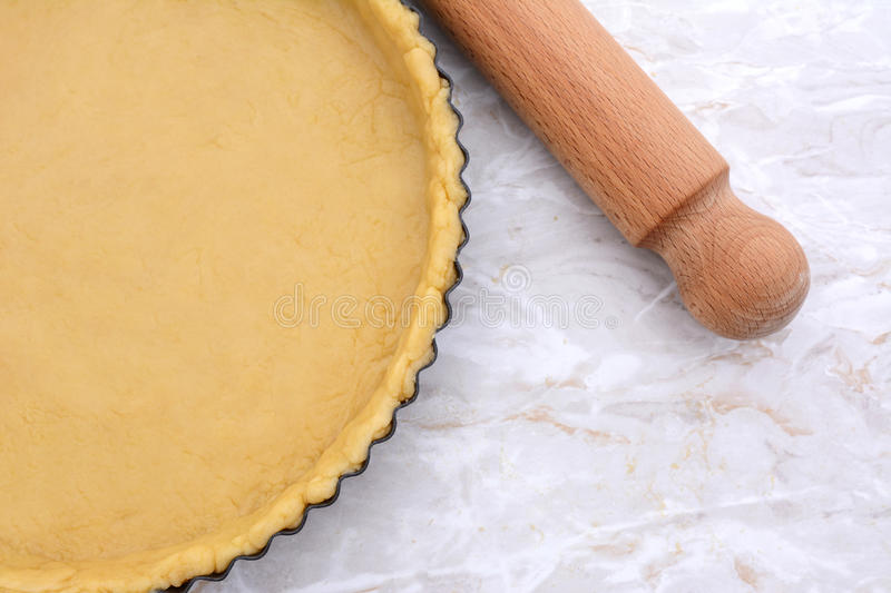 Baking tin lined with pastry, wooden rolling pin beside stock images