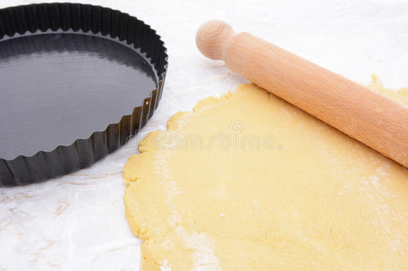 Baking tin next to shortcrust pastry and rolling pin stock photography