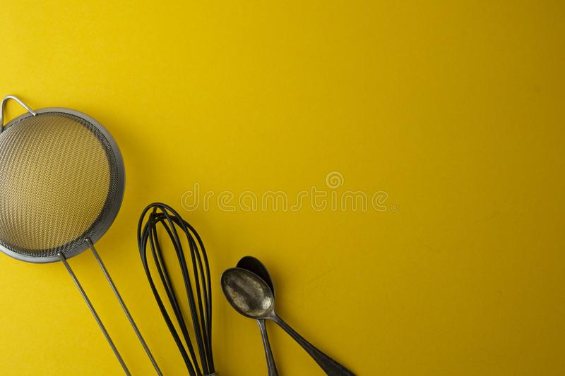 Baking tools for pastry or dessert - sieve, whisk, spoon. Yellow background, flat lay. Cooking process. Copy space royalty free stock images
