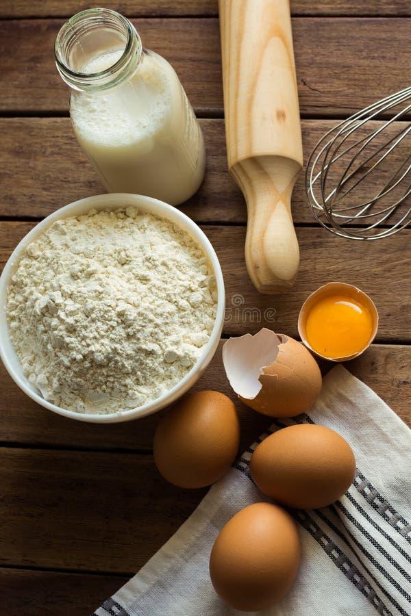 Bakkende ingrediëntenbloem, gebarsten eieren, open dooier, melk, deegrol, linnenhanddoek, rustiek keukenbinnenland, werktuigen royalty-vrije stock foto's