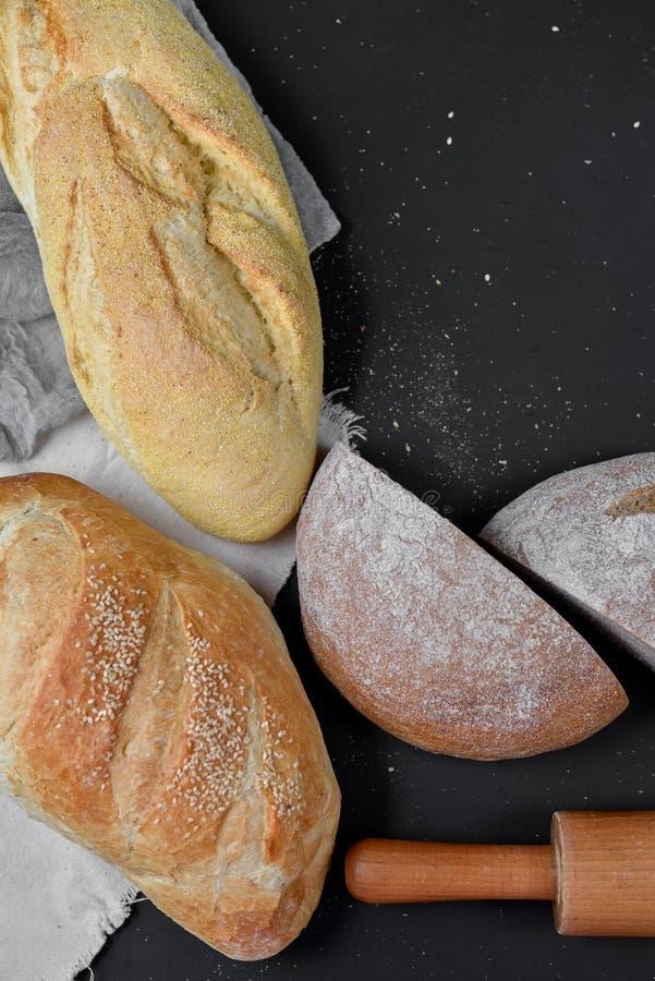 Bakkerij - rustieke knapperige broden van brood en deegrol op zwarte bordachtergrond Stilleven hierboven wordt gevangen die van royalty-vrije stock foto