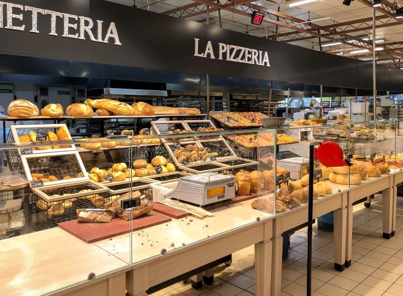Bakkerijafdeling met vers brood op planken binnen van IPER van hypermarket van Varese, Italië royalty-vrije stock afbeelding