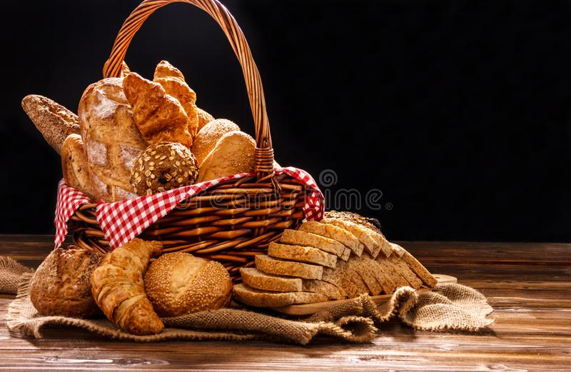 Bakkerijassortiment op houten lijst aangaande donkere achtergrond Stilleven van verscheidenheid van brood met natuurlijk ochtendl stock foto's