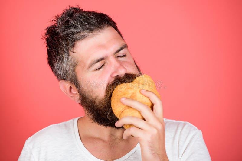 Bakkerijconcept Biting croissant Delicious breakfast Man start morgenochtend met croissant Gedekte hipster geniet van ontbijt stock foto's