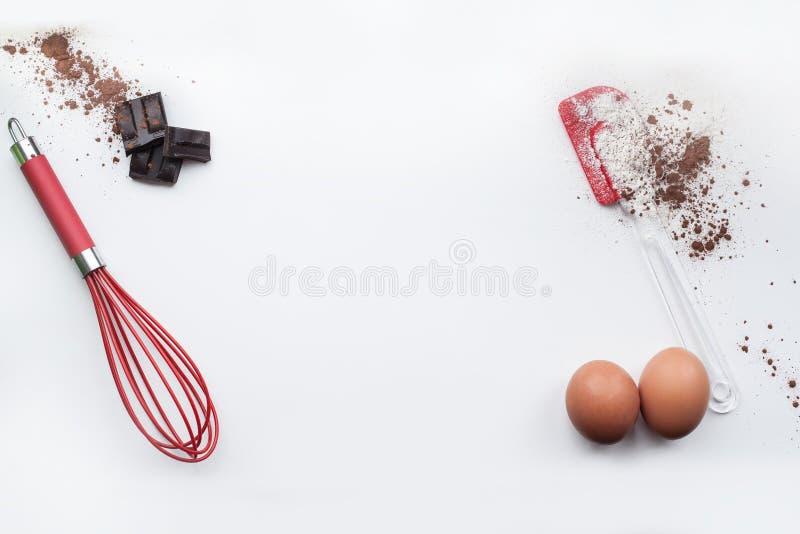 Bakkerijingrediënten - bloem, eieren, cacao, chocolade op witte lijst Het zoete concept van het gebakjebaksel Vlak leg, kopieer r stock afbeeldingen