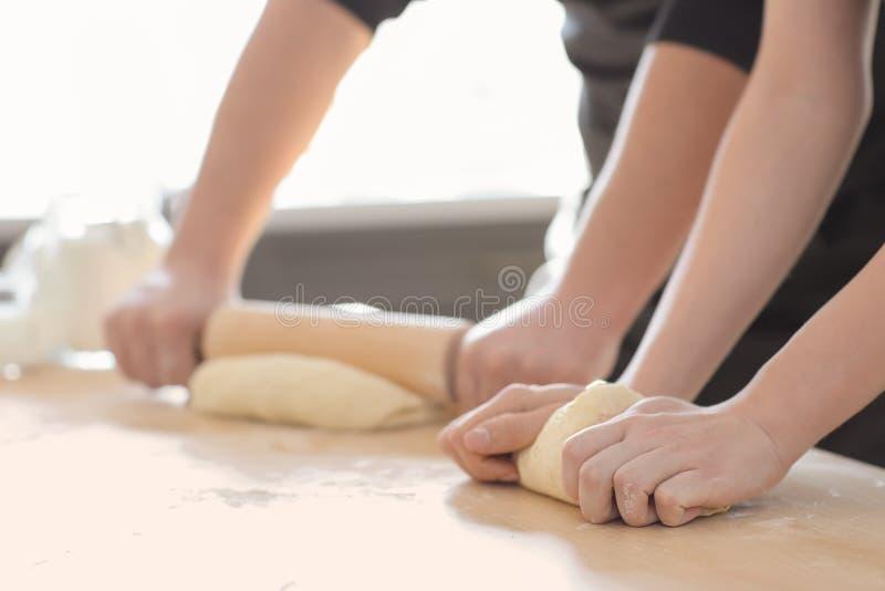 Bakkers die deeg op keukenlijst voorbereiden stock foto's